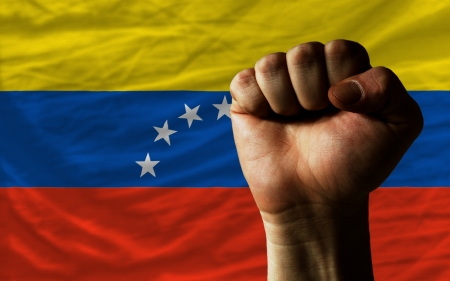 complete national flag of venezuela covers whole frame, waved, crunched and very natural looking. In front plan is clenched fist symbolizing determination photo