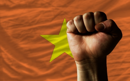 determinism: complete national flag of vietnam covers whole frame, waved, crunched and very natural looking. In front plan is clenched fist symbolizing determination