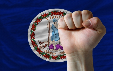 determinism: complete american state of virginia covers whole frame, waved, crunched and very natural looking. In front plan is clenched fist symbolizing determination