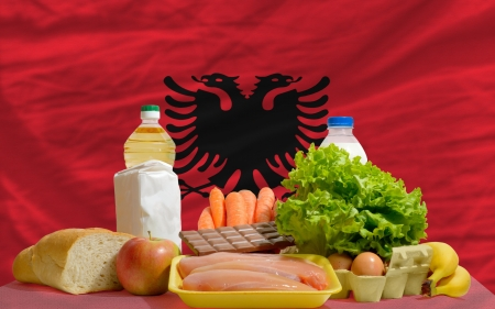 complete national flag of albania covers whole frame, waved, crunched and very natural looking. In front plan are fundamental food ingredients for consumers, symbolizing consumerism an human needs photo