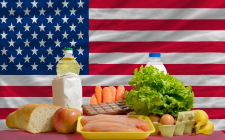 consumerism: complete national flag of us covers whole frame, waved, crunched and very natural looking. In front plan are fundamental food ingredients for consumers, symbolizing consumerism an human needs