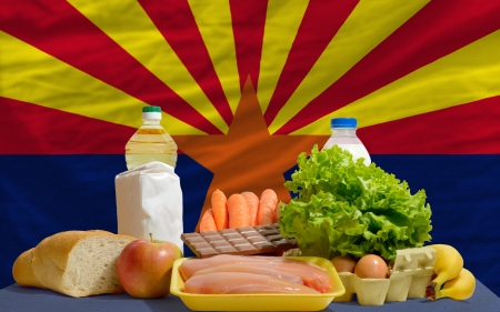 consumerism: complete american state flag of arizona covers whole frame, waved, crunched and very natural looking. In front plan are fundamental food ingredients for consumers, symbolizing consumerism an human needs Stock Photo