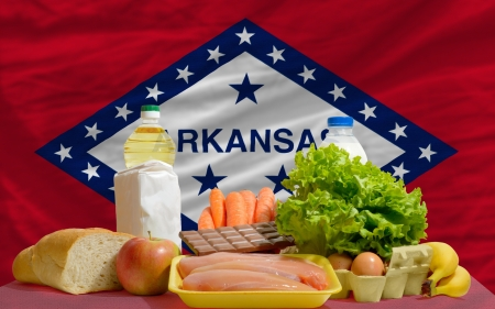 consumerism: complete american state flag of arkansas covers whole frame, waved, crunched and very natural looking. In front plan are fundamental food ingredients for consumers, symbolizing consumerism an human needs Stock Photo