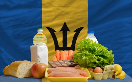 barbadian: complete national flag of barbadian covers whole frame, waved, crunched and very natural looking. In front plan are fundamental food ingredients for consumers, symbolizing consumerism an human needs