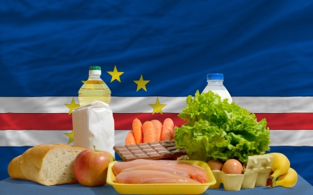 cape verde flag: complete national flag of cape verde covers whole frame, waved, crunched and very natural looking. In front plan are fundamental food ingredients for consumers, symbolizing consumerism an human needs