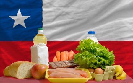 complete national flag of chile covers whole frame, waved, crunched and very natural looking. In front plan are fundamental food ingredients for consumers, symbolizing consumerism an human needs photo