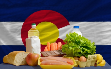 consumerism: complete american state flag of colorado covers whole frame, waved, crunched and very natural looking. In front plan are fundamental food ingredients for consumers, symbolizing consumerism an human needs