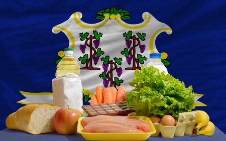 complete american state flag of connecticut covers whole frame, waved, crunched and very natural looking. In front plan are fundamental food ingredients for consumers, symbolizing consumerism an human needs Stock Photo - 13953565