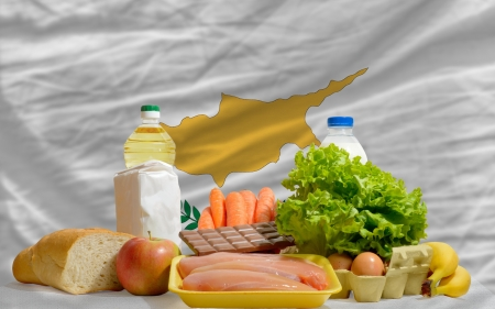 complete national flag of cyprus covers whole frame, waved, crunched and very natural looking. In front plan are fundamental food ingredients for consumers, symbolizing consumerism an human needs photo