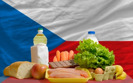consumerism: complete national flag of czech covers whole frame, waved, crunched and very natural looking. In front plan are fundamental food ingredients for consumers, symbolizing consumerism an human needs
