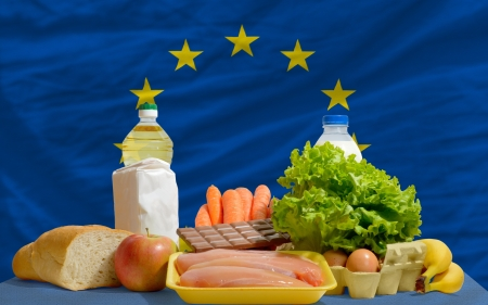 complete national flag of europe covers whole frame, waved, crunched and very natural looking. In front plan are fundamental food ingredients for consumers, symbolizing consumerism an human needs photo