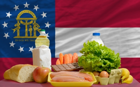 consumerism: complete american state flag of georgia covers whole frame, waved, crunched and very natural looking. In front plan are fundamental food ingredients for consumers, symbolizing consumerism an human needs Stock Photo