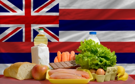 consumerism: complete american state flag of hawaii covers whole frame, waved, crunched and very natural looking. In front plan are fundamental food ingredients for consumers, symbolizing consumerism an human needs Stock Photo