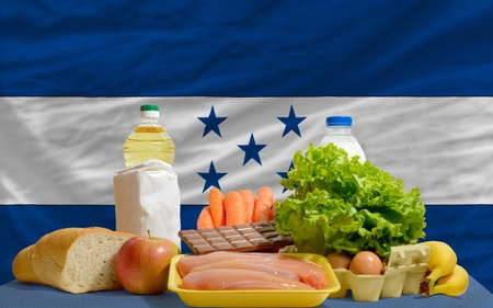 complete national flag of honduras covers whole frame, waved, crunched and very natural looking. In front plan are fundamental food ingredients for consumers, symbolizing consumerism an human needs photo