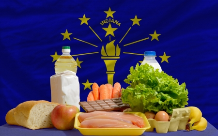 consumerism: complete american state flag of indiana covers whole frame, waved, crunched and very natural looking. In front plan are fundamental food ingredients for consumers, symbolizing consumerism an human needs
