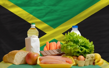 jamaican: complete national flag of jamaica covers whole frame, waved, crunched and very natural looking. In front plan are fundamental food ingredients for consumers, symbolizing consumerism an human needs