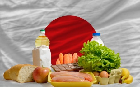 complete national flag of japan covers whole frame, waved, crunched and very natural looking. In front plan are fundamental food ingredients for consumers, symbolizing consumerism an human needs photo