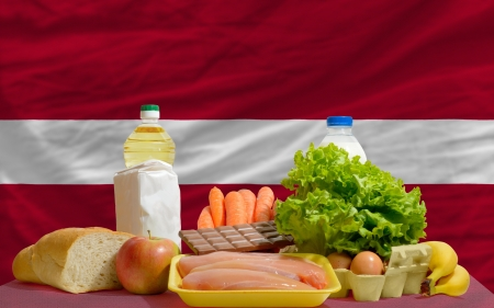 complete national flag of latvia covers whole frame, waved, crunched and very natural looking. In front plan are fundamental food ingredients for consumers, symbolizing consumerism an human needs photo