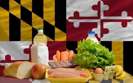 consumerism: complete american state flag of maryland covers whole frame, waved, crunched and very natural looking. In front plan are fundamental food ingredients for consumers, symbolizing consumerism an human needs