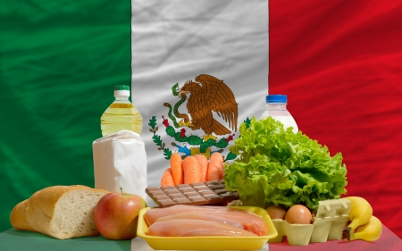 consumerism: complete national flag of mexico covers whole frame, waved, crunched and very natural looking. In front plan are fundamental food ingredients for consumers, symbolizing consumerism an human needs Stock Photo