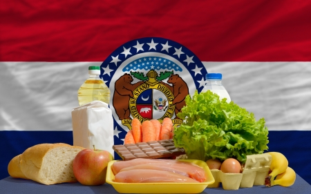 consumerism: complete american state flag of missouri covers whole frame, waved, crunched and very natural looking. In front plan are fundamental food ingredients for consumers, symbolizing consumerism an human needs Stock Photo