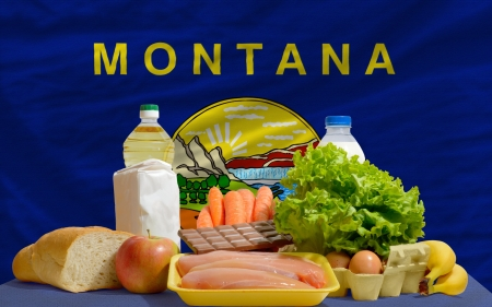 consumerism: complete american state flag of montana covers whole frame, waved, crunched and very natural looking. In front plan are fundamental food ingredients for consumers, symbolizing consumerism an human needs
