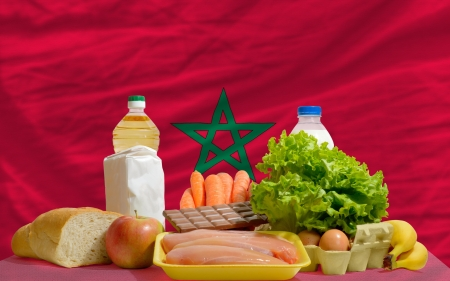 complete national flag of morocco covers whole frame, waved, crunched and very natural looking. In front plan are fundamental food ingredients for consumers, symbolizing consumerism an human needs photo