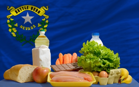 complete american state flag of nevada covers whole frame, waved, crunched and very natural looking. In front plan are fundamental food ingredients for consumers, symbolizing consumerism an human needs photo