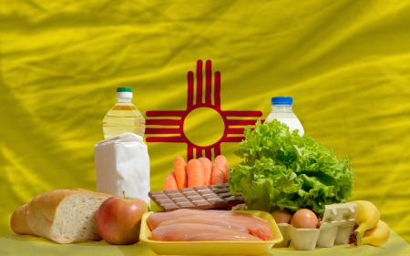 consumerism: complete american state flag of new mexico covers whole frame, waved, crunched and very natural looking. In front plan are fundamental food ingredients for consumers, symbolizing consumerism an human needs