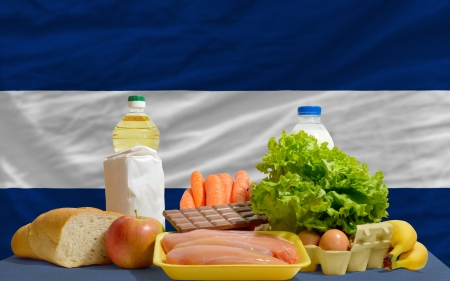 complete national flag of nicaragua covers whole frame, waved, crunched and very natural looking. In front plan are fundamental food ingredients for consumers, symbolizing consumerism an human needs Stock Photo - 13953360