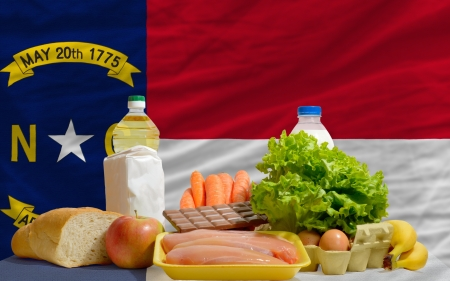 consumerism: complete american state flag of north carolina covers whole frame, waved, crunched and very natural looking. In front plan are fundamental food ingredients for consumers, symbolizing consumerism an human needs Stock Photo