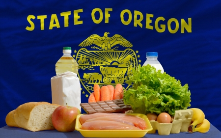 consumerism: complete american state flag of oregon covers whole frame, waved, crunched and very natural looking. In front plan are fundamental food ingredients for consumers, symbolizing consumerism an human needs