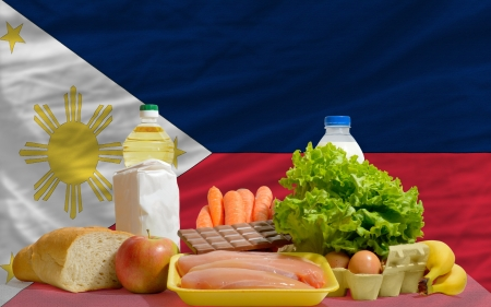 philippines flag: complete national flag of philippines covers whole frame, waved, crunched and very natural looking. In front plan are fundamental food ingredients for consumers, symbolizing consumerism an human needs