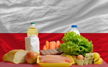 complete national flag of poland covers whole frame, waved, crunched and very natural looking. In front plan are fundamental food ingredients for consumers, symbolizing consumerism an human needs photo