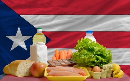 puertorico: complete national flag of puerto rico covers whole frame, waved, crunched and very natural looking. In front plan are fundamental food ingredients for consumers, symbolizing consumerism an human needs