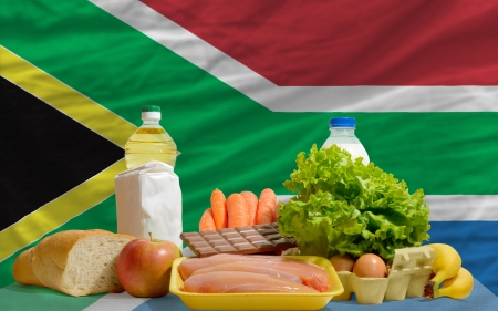 complete national flag of south africa covers whole frame, waved, crunched and very natural looking. In front plan are fundamental food ingredients for consumers, symbolizing consumerism an human needs photo