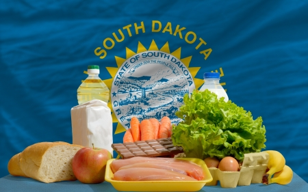 consumerism: complete american state flag of south dakota covers whole frame, waved, crunched and very natural looking. In front plan are fundamental food ingredients for consumers, symbolizing consumerism an human needs