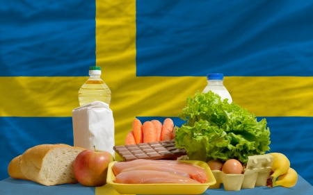 complete national flag of sweden covers whole frame, waved, crunched and very natural looking. In front plan are fundamental food ingredients for consumers, symbolizing consumerism an human needs Stock Photo - 13953258