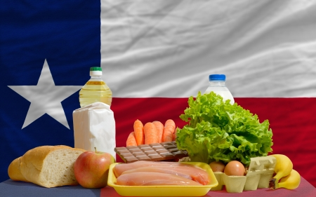 consumerism: complete american state flag of texas covers whole frame, waved, crunched and very natural looking. In front plan are fundamental food ingredients for consumers, symbolizing consumerism an human needs Stock Photo