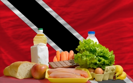 national flag trinidad and tobago: complete national flag trinidad tobago of covers whole frame, waved, crunched and very natural looking. In front plan are fundamental food ingredients for consumers, symbolizing consumerism an human needs