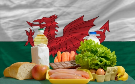 complete national flag of wales covers whole frame, waved, crunched and very natural looking. In front plan are fundamental food ingredients for consumers, symbolizing consumerism an human needs photo
