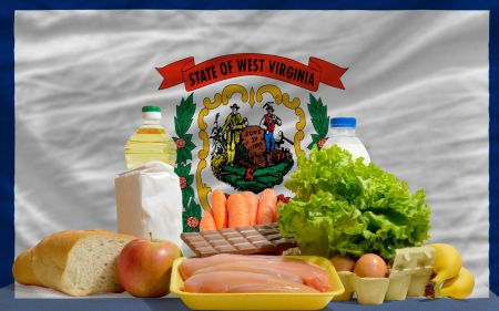 consumerism: complete american state flag of west virginia covers whole frame, waved, crunched and very natural looking. In front plan are fundamental food ingredients for consumers, symbolizing consumerism an human needs Stock Photo