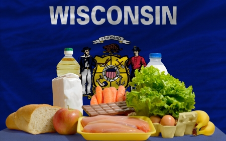 consumerism: complete american state flag of wisconsin covers whole frame, waved, crunched and very natural looking. In front plan are fundamental food ingredients for consumers, symbolizing consumerism an human needs