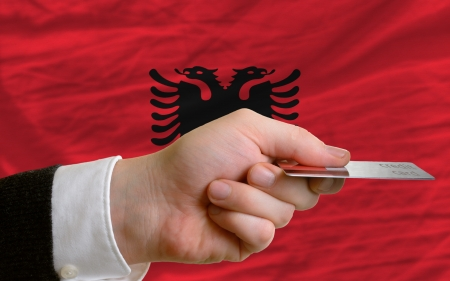 man stretching out credit card to buy goods in front of complete wavy national flag of albania photo