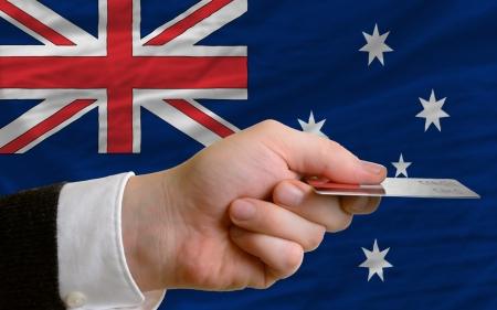 man stretching out credit card to buy goods in front of complete wavy national flag of australia photo