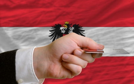 man stretching out credit card to buy goods in front of complete wavy national flag of austria photo