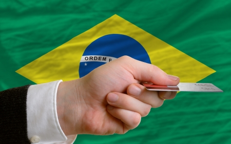 man stretching out credit card to buy goods in front of complete wavy national flag of brazil Stock Photo - 14045571