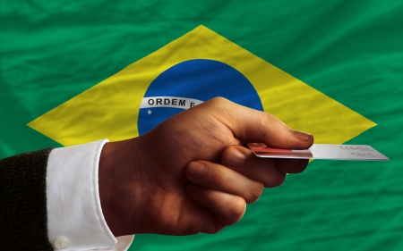 man stretching out credit card to buy goods in front of complete wavy national flag of brazil photo