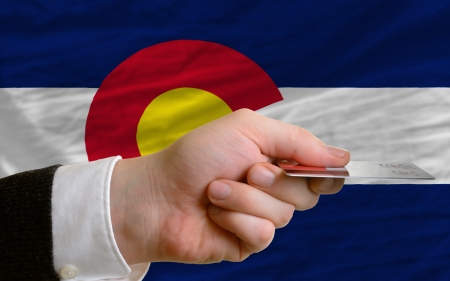 man stretching out credit card to buy goods in front of complete wavy national flag of american state of colorado photo