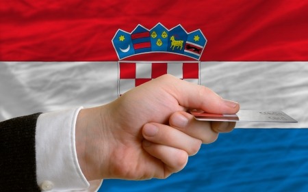 man stretching out credit card to buy goods in front of complete wavy national flag of croatia photo